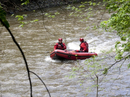 Rescue teams search for a body after a man jumped off a ledge near Ithaca Falls on Tuesday.