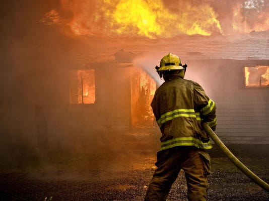 Firefighter spraying water at a house fire