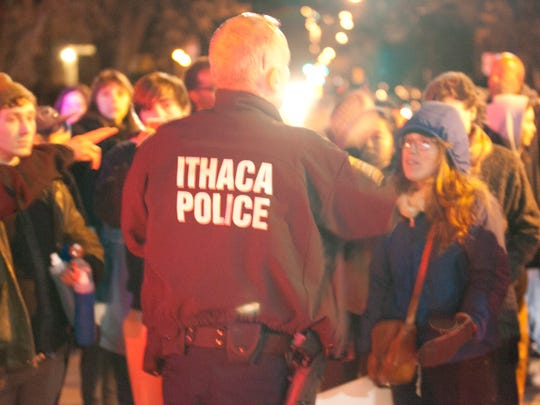 Protesters marched across downtown Ithaca Tuesday night, clogging portions of roads throughout the evening in protest of a Missouri grand jury's decision to not charge police officer Darren Wilson in the shooting death of Michael Brown.