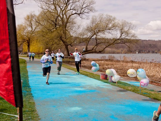 Runners participate in the Color Splash Run on Sunday morning in Stewart Park.