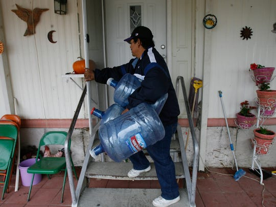 Javier Ramos carries empty water bottles to refill in order to avoid drinking contaminated tap water at his mobile home in Thermal.