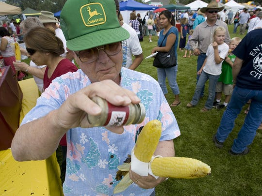 Chuck Martin sprinkles pepper on his ears of roasted corn at the Enterprise Cornfest.