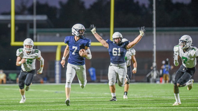 Mill Valley lineman Ethan Kremer (61) celebrates as Jaguar quarterback Cooper Marsh (7) sprints for a touchdown during Mill Valley's opener with Derby. In a clash of last year's Class 6A and 5A state champions, Mill Valley turned in a stunning 45-14 rout of the Panthers.