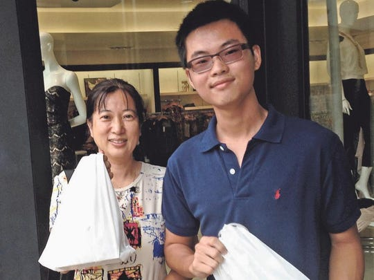 Alice Yang and her nephew, Peter Ear, got in line Friday at the Coconut Point Apple store at 9 a.m. and emerged at 2 p.m. with their iPhones.