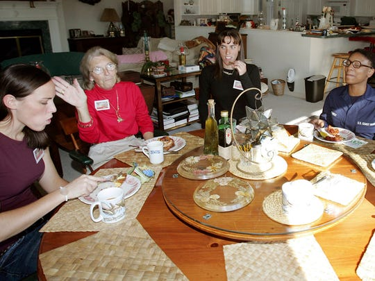 In this Thursday, Nov. 22, 2007, file photograph, U.S. Coast Guard recruits Stephanie Perez, right, and Angela Kennedy, second right, along with Kristina Gscheidle, left, and Emily Gscheidle, center, enjoy a Thanksgiving brunch at the home of Ginny Beale, second left, in Lower Township, N.J.