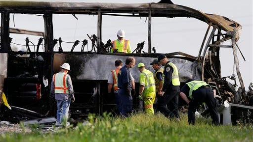 In this April 11, 2014, file photo, officials and California Highway Patrol Officers look over the remains of a tour bus that was struck by a FedEx truck on Interstate 5 in Orland. More than a year after the fiery wreck, authorities have announced the cause of the head-on collision north Sacramento.