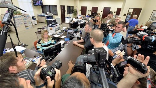Surrounded by the media, David Moore, center, and his partner David Ermold attempt to apply for a marriage license at the Rowan County Courthouse in Morehead, Ky., Tuesday, Sept. 1, 2015. Although her appeal to the US Supreme Court was denied, Rowan County Clerk Kim Davis still refuses to issue marriage licenses. (AP Photo/Timothy D. Easley)