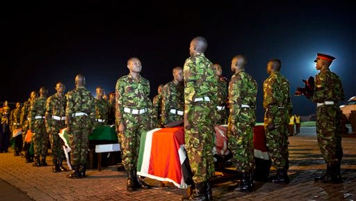 FILE - In this Monday, Jan. 18, 2016 file photo, military pallbearers stand to attention next to the coffins of four Kenyan soldiers who were killed in an attack by al-Shabab in Somalia, at a ceremony to receive their bodies which were airlifted to Wilson Airport in Nairobi, Kenya. The number of deadly attacks by Islamic extremists is mounting across Africa, raising questions about the resurgence of armed groups once seen to be in decline. (AP Photo/Ben Curtis, File)
