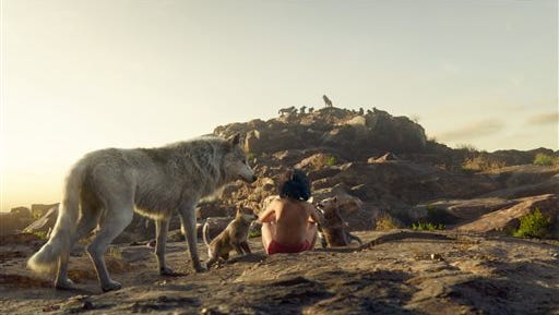 "In this image released by Disney, Mowgli, portrayed by Neel Sethi, center, and Raksha the wolf, voiced by Lupita Nyong'o, appear in a scene from, ""The Jungle Book."""