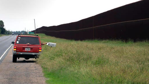 In this Monday, Nov. 14, 2016, photo, a carrier delivers mail along a section of border fence in Brownsville, Texas. The idea of a concrete wall spanning the entire 1,954-mile southwest frontier collides head-on with multiple realities, like a looping Rio Grande, fierce local resistance, and cost.