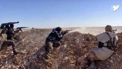 FILE - This file frame grab from a video provided on Monday, March 6, 2017 by the Syria Democratic Forces (SDF), shows fighters from the SDF opening fire on an Islamic State group's position, in Raqqa's eastern countryside, Syria. The Kurdish-led Syrian Democratic Forces is likely to lead the operation to capture the northern Syrian city of Raqqa from the Islamic State group in the coming weeks as the forces presses in its offensive against the extremists in areas close to their de facto capital.