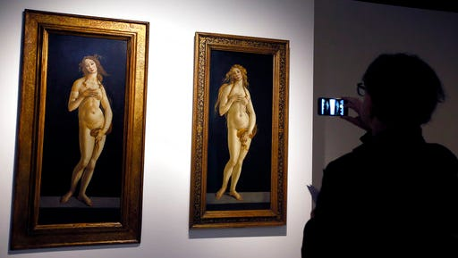 """FILE- In this Wednesday, March 2, 2016 file photo a person photographs a painting by Sandro Botticelli called 'Venus' during the press view for the V&A's spring exhibition Botticelli Reimagined, in London. A new exhibition of Italian Renaissance master Sandro Botticelli's paintings opens this weekend in Boston, """"Botticelli and the Search for the Divine"""" at Boston's Museum of Fine Arts."""