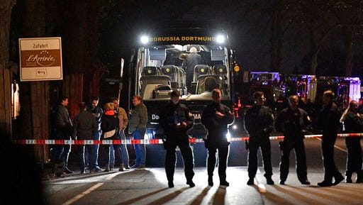 FILE - In this April 11, 2017 file photo police officers stand in front of Dortmund's damaged team bus after explosions which injured two people before the Champions League quarterfinal soccer match between Borussia Dortmund and AS Monaco in Dortmund, western Germany.