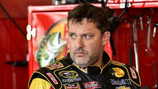 In this Friday, Aug. 8, 2014, photograph, Tony Stewart stands in the garage area after a practice session for the NASCAR Sprint Cup Series auto race at Watkins Glen International in Watkins Glen, N.Y.