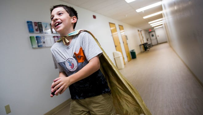 Tyler Carash, otherwise known as Donut Boy, runs through the halls of the Lee County Sheriff's Office in Fort Myers, thanking officers for their service on Tuesday, June 27, 2017. Tyler, 9, is on a mission to deliver donuts and coffee to all of the cops in America.