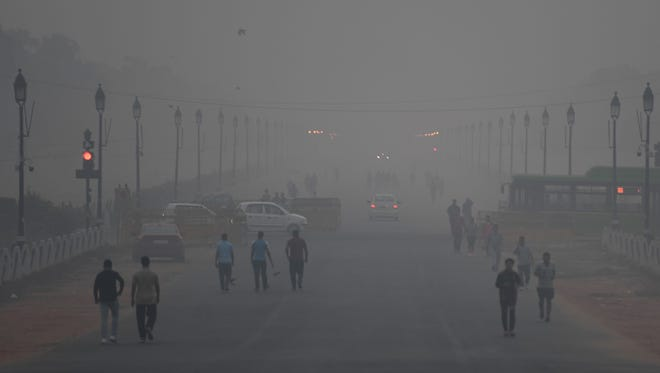 Indian pedestrians walk amid heavy smog conditions in New Delhi on Nov. 2, 2018.  Smog levels spike during winter in Delhi, when air quality often eclipses the World Health Organization's safe levels.