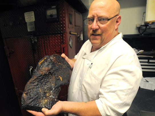 Chef Michael Keys, showing off a smoked brisket, takes