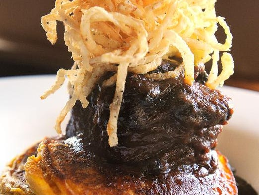 The Coca-Cola marinated beef short rib entrée brings together a harmony of regional and seasonal elements — collards cooked with Benton's bacon, sweet potato pancakes, Farmer Dave's green apples and crisp bracelets of onion.