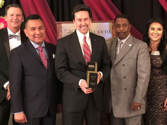 Jon Barela, center, CEO of the Borderplex Alliance, accepts award from CurtisRosemond, right, CEO of the Las Cruces Hispanic Chamber of Commerce, at chamber's awards banquet Feb. 6 in Las Cruces.