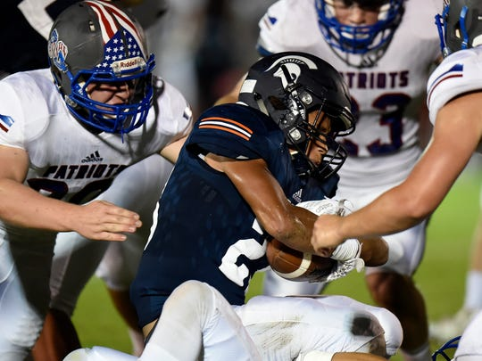Summit running back George Odimegwu, center, is brought down by Page defenders during the first half of an high school football game Friday, Sept. 22, 2017, in Thompson's Station, Tenn.