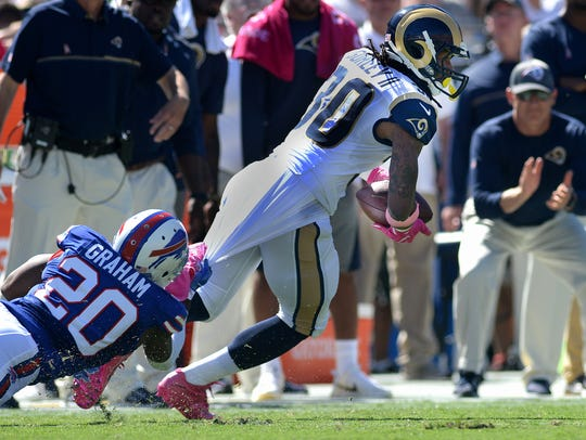 The Rams' Todd Gurley, right, is taken down by the