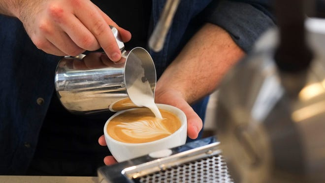 Barista Ryan Riddell pours a latte at Honeybee Coffee Company on Tuesday, Jan. 10, 2017, in South Knoxville.