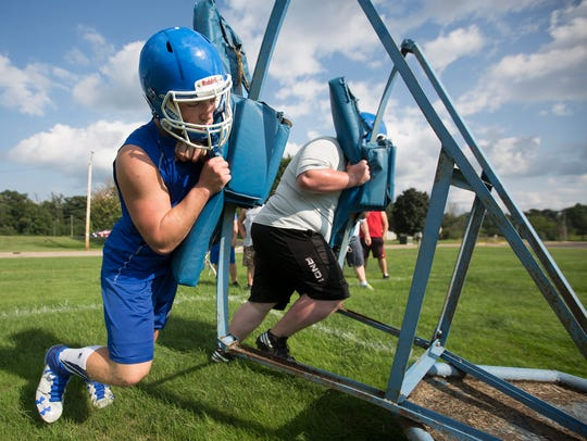 Assumption football players run through drills on the