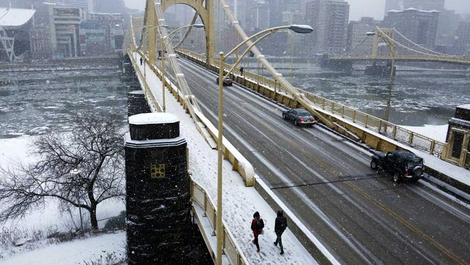 People walk across the Rachel Carson bridge across the Allegheny River toward downtown Pittsburgh as snow falls, Wednesday, Jan. 20, 2016.
