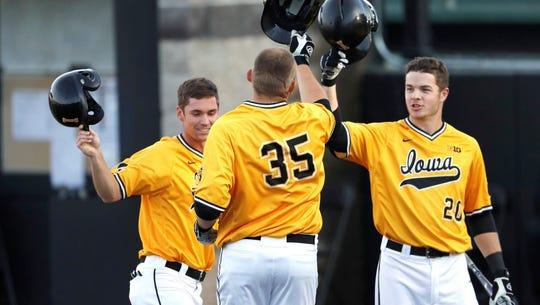 Jake Adams (35) celebrates a home run with his Iowa