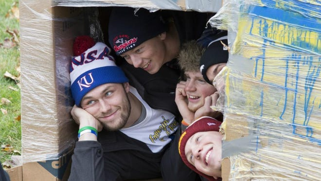 Members of Simpson College's Alpha Tau Omega fraternity huddle in a cardboard box during an annual charity event for Hope Ministries in Des Moines.