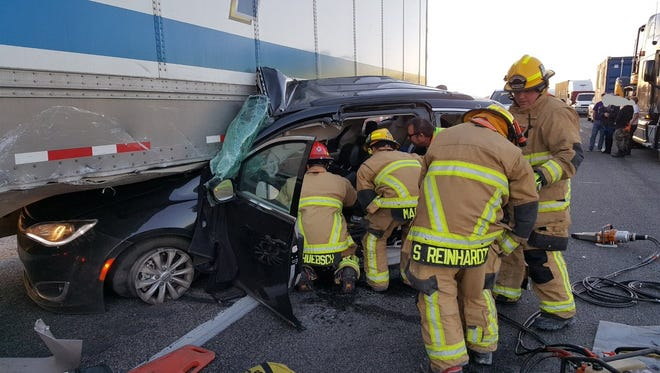 Firefighters work to extricate victims from a vehicle that collided with a semi on Interstate 10 west of Phoenix.