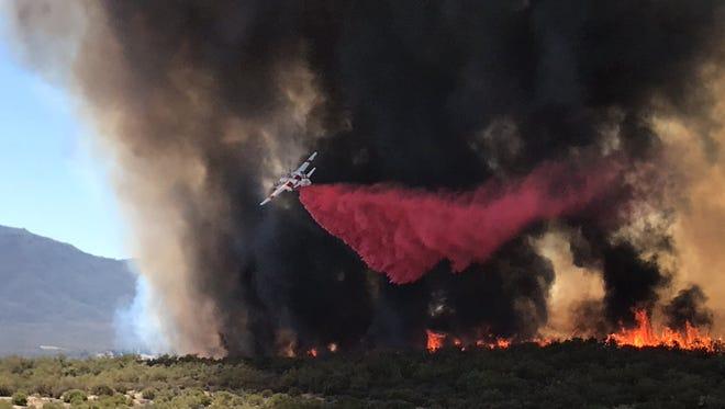 A plane drops a retardant on the Benton fire near Anza.