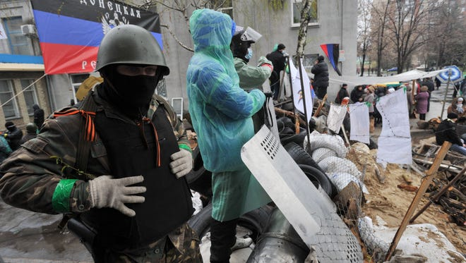 Pro-Russia activists guard a barricade outside a regional police building seized by armed separatists in Slovyansk on Sunday.
