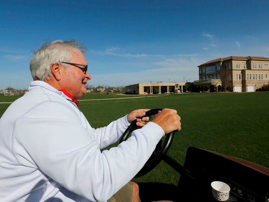 Dennis Albaugh drive a golf car on his 19-hole private golf course, Talons of Tuscany, in northeast Ankeny in this 2014 file photo.