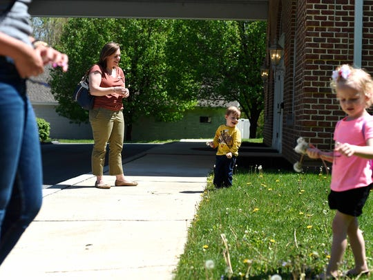 After voting, Kathryn Garber watches as her son, 2-year-old Henry, pick dandelions in Springettsbury Township. Garber voted for Hillary Clinton because she says Hillary will do more for gun control.
