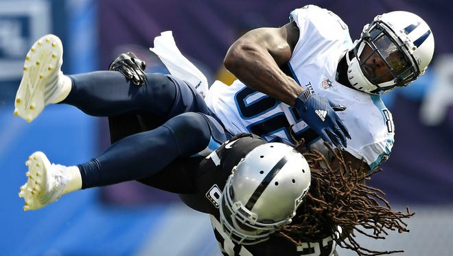 Oakland Raiders free safety Reggie Nelson (27) hits Tennessee Titans tight end Delanie Walker (82) in the second half at Nissan Stadium Sunday, Sept. 10, 2017 in Nashville, Tenn.