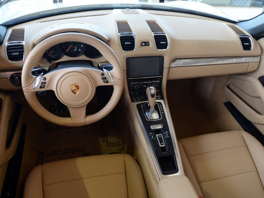 The interior of this  2016 Porsche Boxster convertible is done in a cream colored leather with black accents and chrome trim.