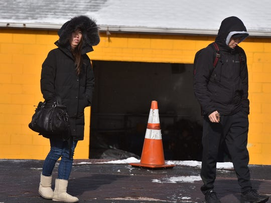 Commuters wait for a bus in Fort Lee on a blustery cold Saturday morning.