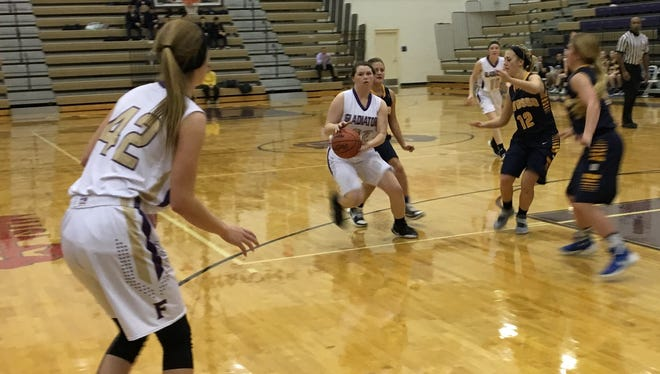 Fowlerville's Jackie Jarvis prepares to pass the ball to Averie Latson during a 61-36 victory over Owosso.