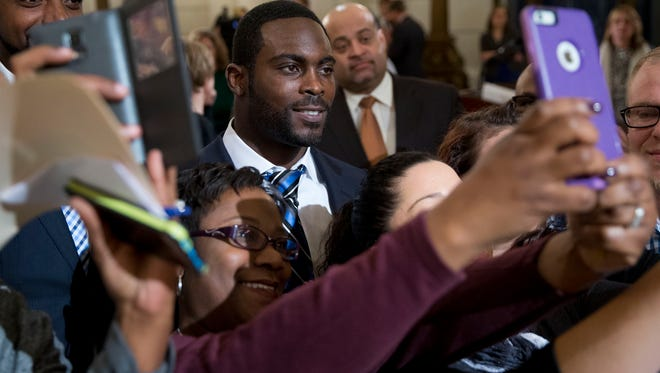 Pittsburgh Steelers quarterback Mike Vick poses for selfies after a news conference Tuesday, Dec. 8, 2015, at the state Capitol in Harrisburg, Pa. Vick is lobbing Pennsylvania legislators on a bill that would help protect pets left in hot cars. Vick was a star quarterback for the NFL's Atlanta Falcons when he pleaded guilty in 2007 to being part of a dogfighting ring and ended up serving 21 months in prison. (AP Photo/Matt Rourke)