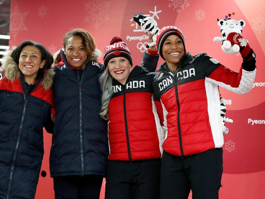From left, siver medalists driver Elana Meyers Taylor and Lauren Gibbs of the United States and bronze medalists driver Kaillie Humphries and Phylicia George of Canada, celebrate during the women's two-man bobsled final at the 2018 Winter Olympics in Pyeongchang, South Korea, Wednesday, Feb. 21, 2018. (AP Photo/Andy Wong)