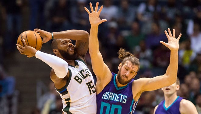 Milwaukee Bucks center Greg Monroe grabs a loose ball in front of Charlotte Hornets forward Spencer Hawes  during the first quarter.