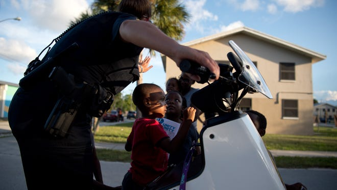 Stuart Police Department Officer Amy Duran lets Tykerion Palmer (center), 5, of Stuart, hit a siren on her patrol vehicle July 25, 2016, as she entertains other children outside Stuart Housing Authority apartments in East Stuart.
