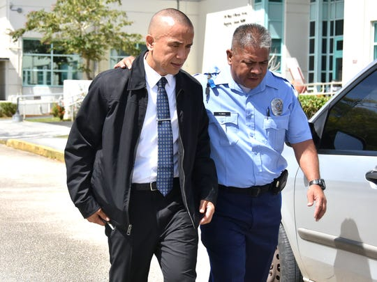 Guam Police Officer Barry Flores, right, walks alongside Lt. Mark Torre as they exit the Guam Judiciary after testifying in a motion hearing in the murder trial of Torre's son, former Officer Mark Torre Jr., on Jan. 27.