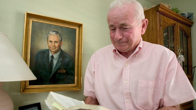 This is Col. Thomas Schaefer in a 2004 photo in his Scottsdale home. Schaefer was the military attache at the U.S. Embassy in Tehran Iran when he and 51 other Americans were held hostage for 444 days. Schaefer is  looking at the Bible he carried through the whole ordeal. He used the Bible to keep a secret code and a diary of everyday life.