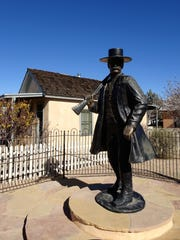 A statue of Wyatt Earp stands in Tombstone near a house