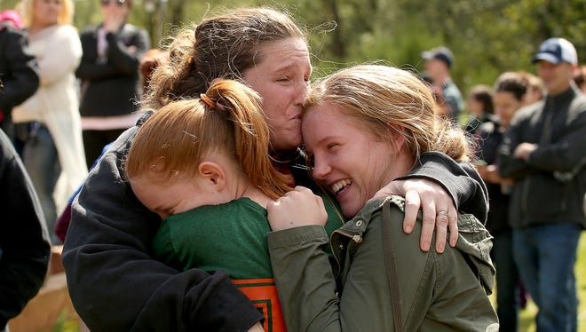 Sandy Johnson embraces her daughters, 11-year-old Audrey and 14-year-old Amber following a scare at Hawkins Middle School in Belfair on April 26.