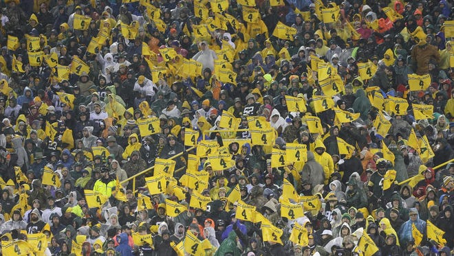 Fans wave their Favre flags during the second quarter against the Chicago Bears at Lambeau Field on Nov. 26, 2015.