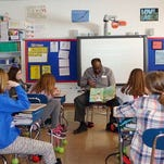 Corning Inc. employees Judith Rowe reads to students at Big Flats Elementary as part of the African-American Read-in program.