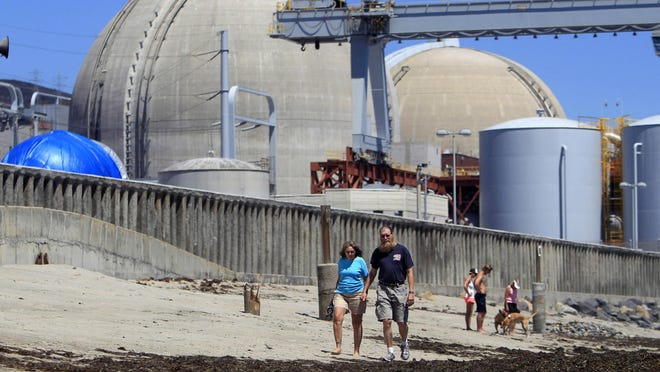 FILE - In this June 30, 2011, file photo, beach-goers walk on the sand near the San Onofre nuclear power plant in San Clemente, Calif. The plant was shut down in 2012. Closed nuclear reactors are dipping into funds set aside for their eventual dismantling to build waste storage on-site, raising questions about whether there will be enough money when the time comes. (AP Photo, Lenny Ignelzi, File)
